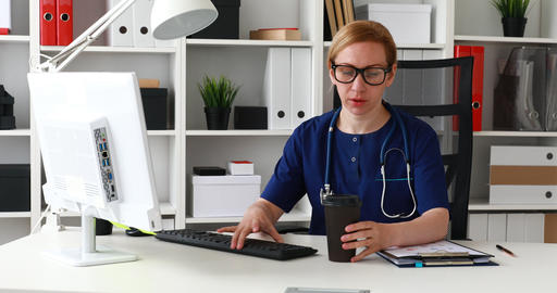 female doctor sitting at workplace and drinking from cup Footage