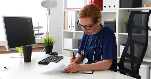 doctor sitting at workplace and working on tablet Live Action