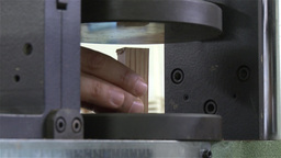 man puts a piece of wood on a machine to test constant loading pressure Footage
