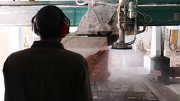worker watching industrial saw sawing huge block of marble stone , slider shot Footage