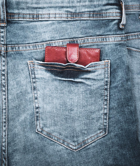 leather purse lies in the back pocket of blue jeans Fotografía