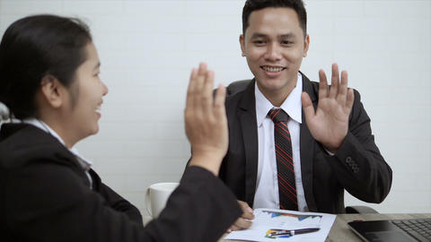 Asian business man and woman hi five touch hand GIF