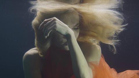 Portrait blonde woman in orange dress swimming underwater on dark background Footage