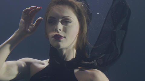 Portrait beautiful woman in black dress swimming underwater on dark background Footage