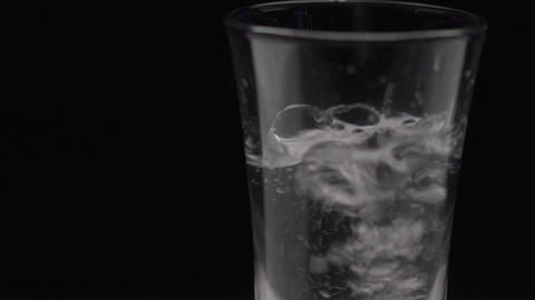 Pour alcohol into the glass. A glass of vodka on the table. The sweating glass Footage