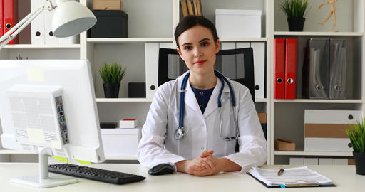 doctor sitting at workplace raising hand to chin and looking at camera Live Action