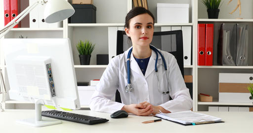 medical worker examining medical card in office Live Action