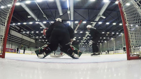 skilled goalkeeper in black defends goal at hockey match Live Action