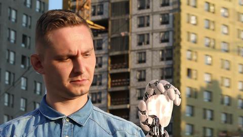 [alt video] Man Looks on His Robotic Hand