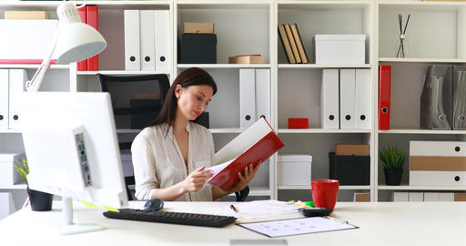 businesswoman in black skirt putting folder in cabinet Live Action