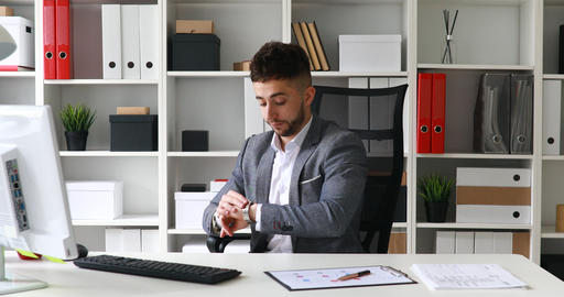 businessman in gray jacket sitting at table in white office, looking at clock Live Action