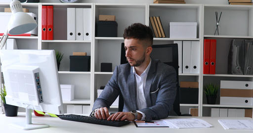 businessman in gray jacket sitting at table in white office, printing on the Live Action