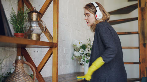 Joyful young lady is dusting the furniture, listening to music with headphones Footage