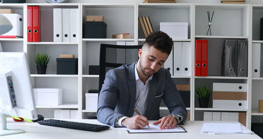 businessman in gray jacket sitting at table in white office and signing Live Action
