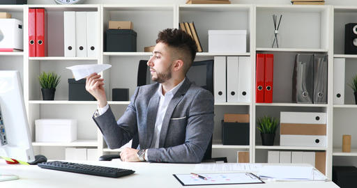 businessman in gray jacket in white office and launching paper airplane Live Action