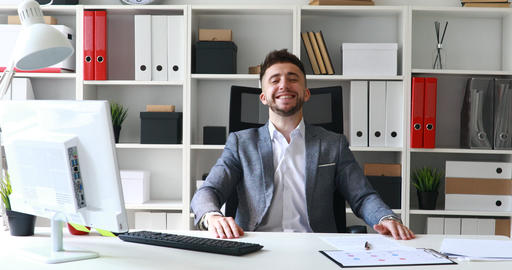 businessman in gray jacket sitting at table in white office and rejoicing at Live Action