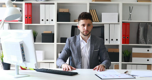 director in gray jacket sitting at table in white office and shaking head Live Action