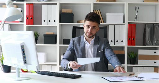 businessman in gray jacket sitting at table in white office and offering Live Action