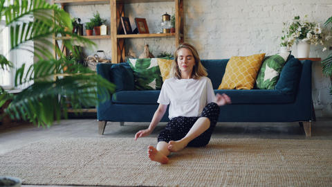 Pretty young woman is practising yoga at home relaxing in simple body position Footage