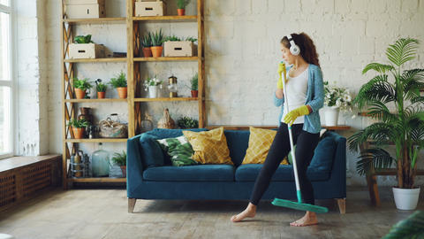 Cheerful young woman is dancing with mop during routine clean-up in nice loft Live Action