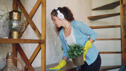 Attractive housewife is dusting the furniture and listening to the radio through Footage