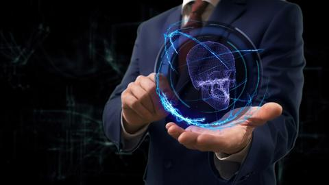 Businessman shows concept hologram 3d skull on his hand Photo