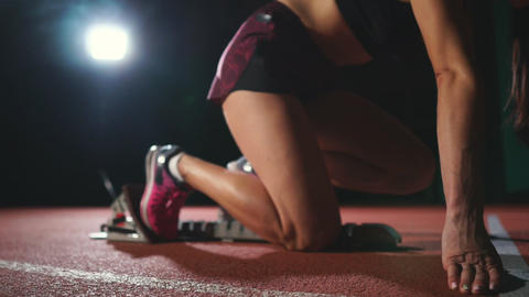 Female athlete on a dark background to run the sprint of the cross country pad Live Action