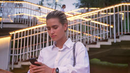 Lovely modern woman is standing on bridge, watching in smartphone, watching at Footage