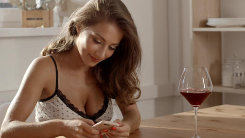 Sexy and attractive woman in candid dress sits at the table in a cafe with glass Footage