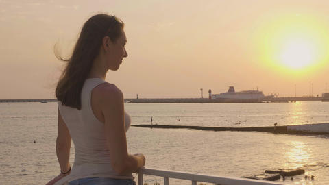 Young woman looking at evening sunset in sea. Evening sky landscape Footage