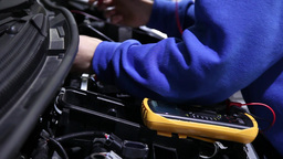 mechanic checks battery power with a multimeter, slider shot Footage