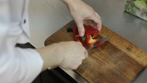 Close up of a chef slicing a red bell pepper on a wooden cutting board.Close-up  Footage