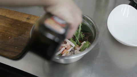 chef cooking a vegetable salad with seafood. Close-up of chef hands cooking and  Live Action