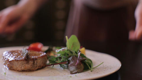 waiter puts pork steak on a table in a restaurant. closeup. Serving Food Footage
