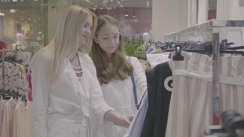 Two girls look and choose a dress in clothes shop Footage