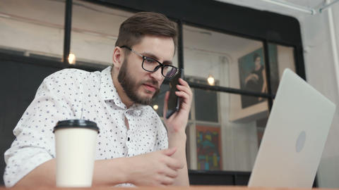 Man in office talking at phone and type at laptop GIF