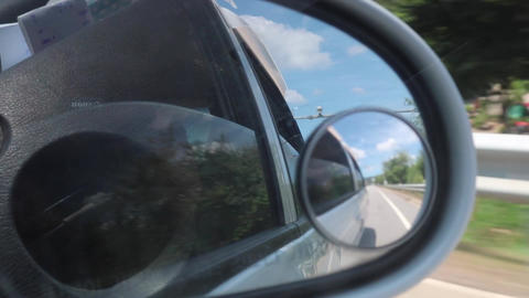 Side mirror rear view scenery in a moving car Live Action