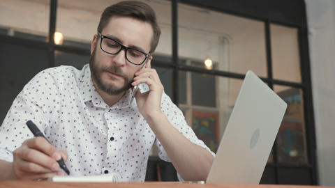 Man talking at smartphone and writing in office GIF