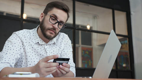 Man using online banking with laptop and card GIF