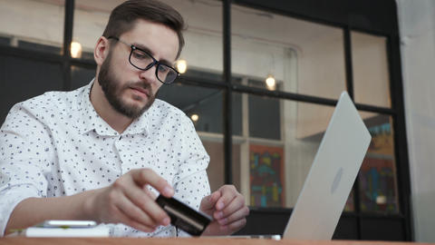 Man paying online by bank card at laptop Footage