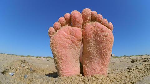 Feet legs strewn sprinkled with sand sanded on the sandy beach Footage