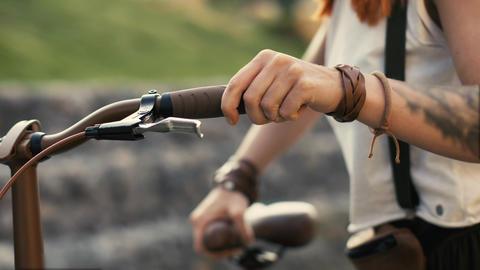 Woman legs walking beside riding bike on city road. Woman feet and bicycle wheel Photo