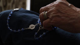 Rosary beads being picked up by elderly christian woman. Close up of religious Footage