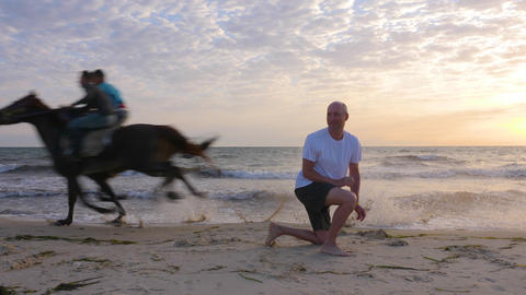 Sportsman exercising on seashore while mad riders running on horses near him Footage