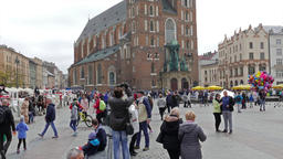 Krakow, Poland. St. Mary's Basilica and peole strolling in the old town square Live Action