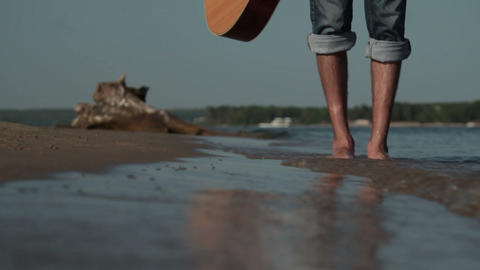 A young man walking on the beach. Walk on the beach.Close-up legs.Man walks on Live Action