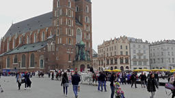 Krakow, Poland. St. Mary Basilica and tourists strolling in the old town square Live Action