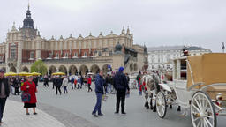 The Krakow Cloth Hall, Sukiennice, horse cabs and strolling tourists Live Action