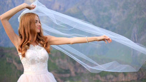 bride in a beautiful tender wedding dress is holding a wedding veil Footage
