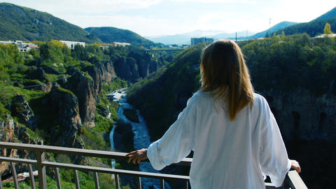 Woman stands at balcony and looks on river flowing in deep narrow gorge Footage